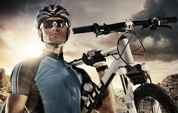 Картинка небо, солнце, облака, пейзаж, тучи, велосипед, поза, камни, фон, очки, футболка, перчатки, шлем, спортсмен, мужчина, …