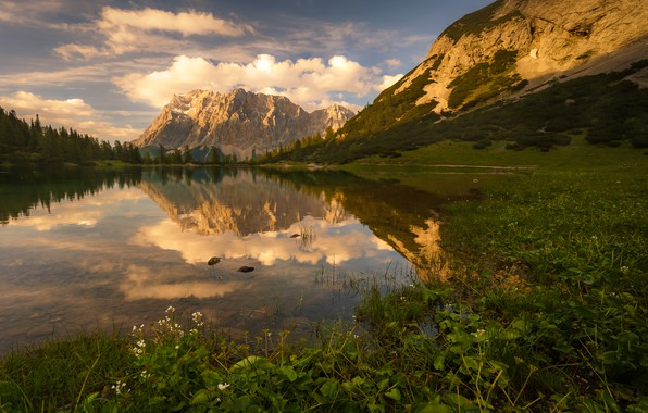 Картинка зелень, лес, лето, небо, трава, листья, облака, горы, озеро, отражение, камни, берег, растительность, вершины, дно, …