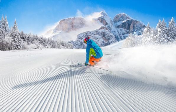Картинка зима, лес, небо, солнце, снег, деревья, пейзаж, горы, скалы, спуск, шапка, лыжи, палки, скорость, склон, …