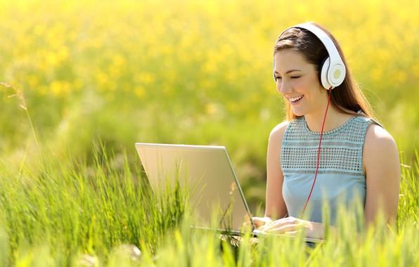 Картинка зелень, поле, трава, девушка, солнце, поза, улыбка, настроение, макияж, наушники, платье, прическа, ноутбук, шатенка, боке