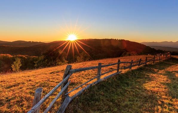 Картинка небо, трава, солнце, лучи, деревья, горы, рассвет, забор, поля, луг, леса