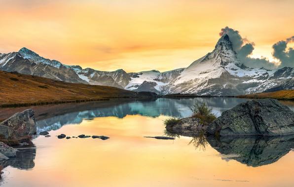 Картинка осень, небо, облака, снег, горы, озеро, отражение, камни, скалы, берег, желтое, водоем, водная гладь, булыжники, ...