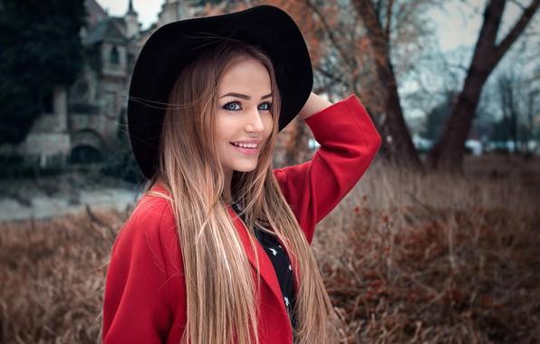 Картинка деревья, природа, поза, улыбка, фон, модель, портрет, шляпа, макияж, прическа, красотка, стоит, в красном, пальто, ...