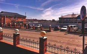 Картинка небо, закат, машины, город, забор, здания, трасса, знаки, база, стоянка, объект, Сургут, керпичный