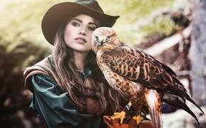 Обои взгляд, девушка, лицо, фон, друг, птица, портрет, шляпа, шатенка, сокол, хищная, размытый, питомец, длинноволосая, пестрая