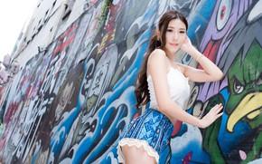 Картинка поза, граффити, модель, шорты, портрет, макияж, майка, фигура, прическа, шатенка, азиатка, стоит, сексуальная, у стены