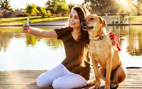 Картинка морда, девушка, солнце, деревья, поза, улыбка, пруд, собака, ошейник, шатенка, мостки, боке, сидят, смартфон, селфи, …