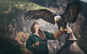 Обои лес, девушка, горы, природа, поза, темный фон, птица, орел, портрет, крылья, руки, куртка, шатенка, перчатка, ...