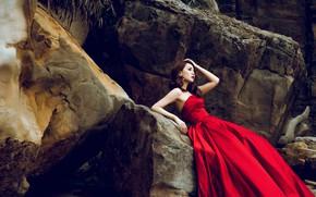 Обои взгляд, девушка, лицо, поза, камни, настроение, скалы, растения, руки, азиатка, сидит, красное платье, огромные, глыбы