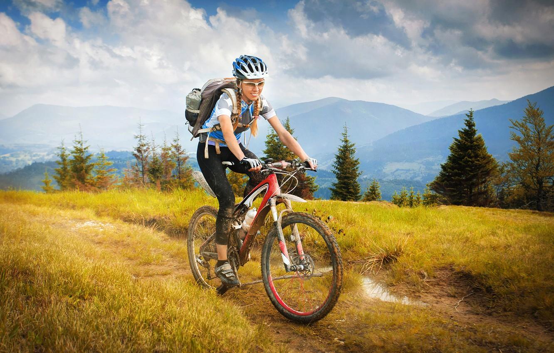 Фото обои трава, девушка, облака, деревья, пейзаж, горы, велосипед, спорт, грязь, очки, футболка, перчатки, шлем, косички, рюкзак, …