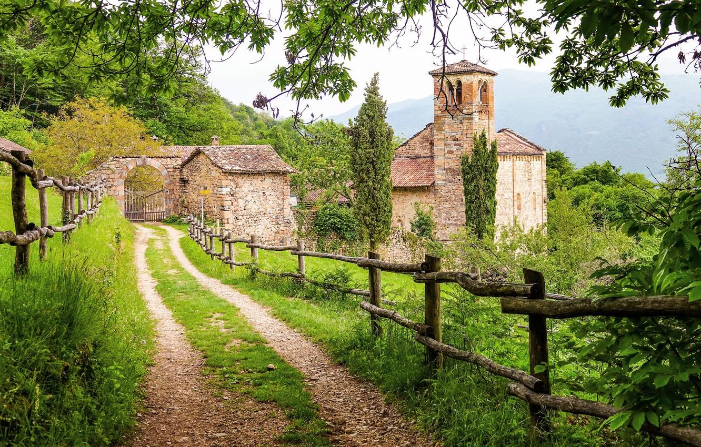 Фото обои дорога, зелень, лето, трава, деревья, горы, ветки, замок, растительность, листва, забор, ворота, ограждение, церковь, дымка, …