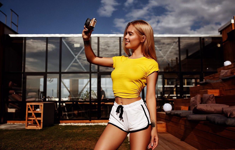 Фото обои girl, shorts, long hair, legs, photo, photographer, camera, model, tattoo, blonde, belly, smiling, t-shirt, tummy, …