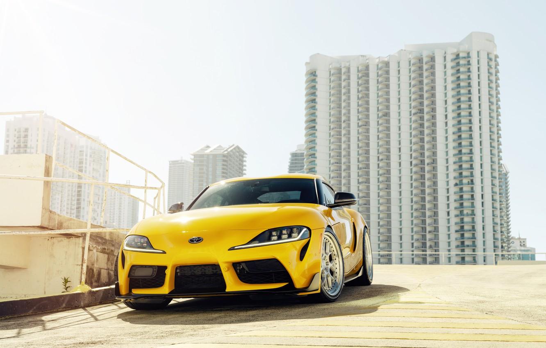Фото обои жёлтый, здания, спорткар, вид спереди, Toyota Supra, 2020 Toyota GR Supra