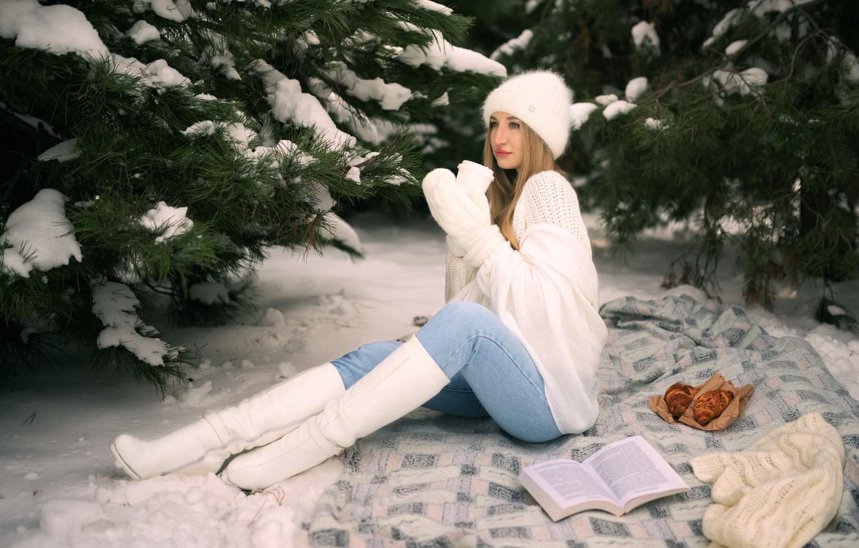 Фото обои зима, девушка, снег, деревья, шапка, джинсы, сапоги, блондинка, книга, сосны, пикник, стаканчик, выпечка, подстилка, свитер, …