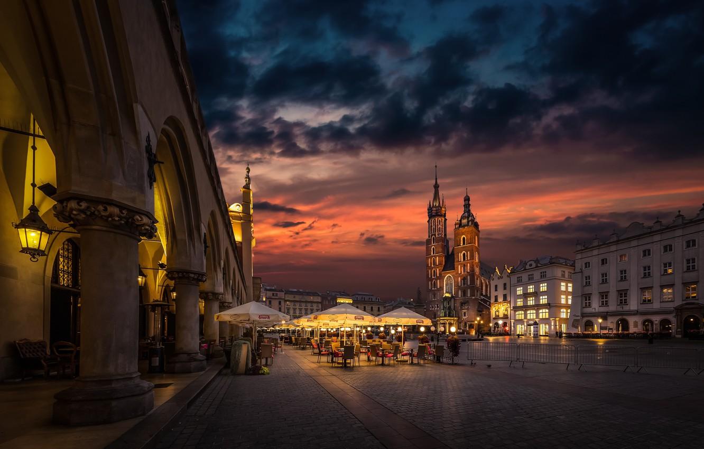 Фото обои город, здания, дома, вечер, освещение, площадь, Польша, зонтики, кафе, башни, столики, костёл, Краков