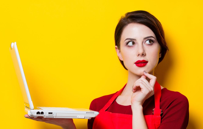 Фото обои девушка, поза, жёлтый, фон, стена, портрет, макияж, прическа, ноутбук, шатенка, стоит, в красном, симпатичная, держит, ...
