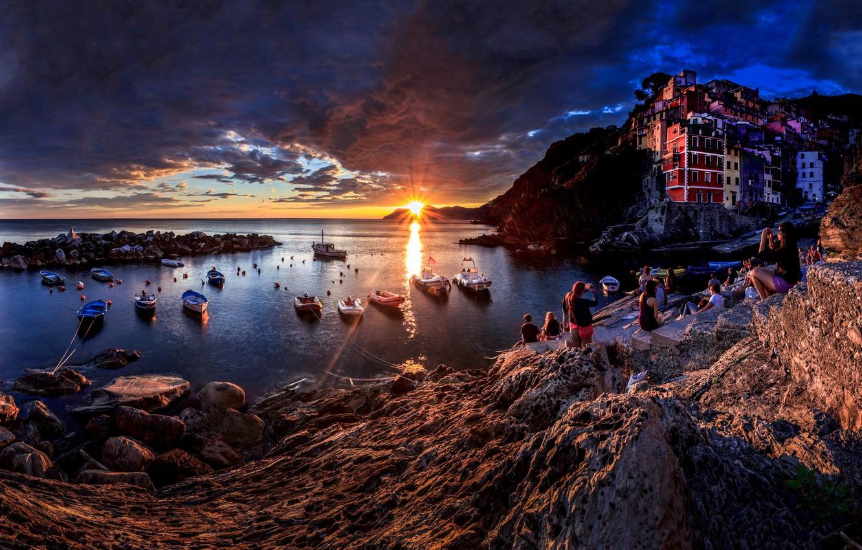 Фото обои море, солнце, лучи, пейзаж, закат, тучи, люди, скалы, дома, лодки, Италия, городок, Riomaggiore, туристы, Риомаджоре, …